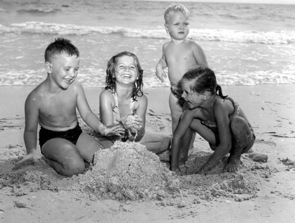 Children Playing In The Sand At Beach