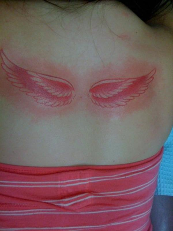 Pink Wings Below Neck Tattoo