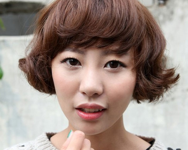 Angular bangs and wavy bob cut hair with slight curly look makes the