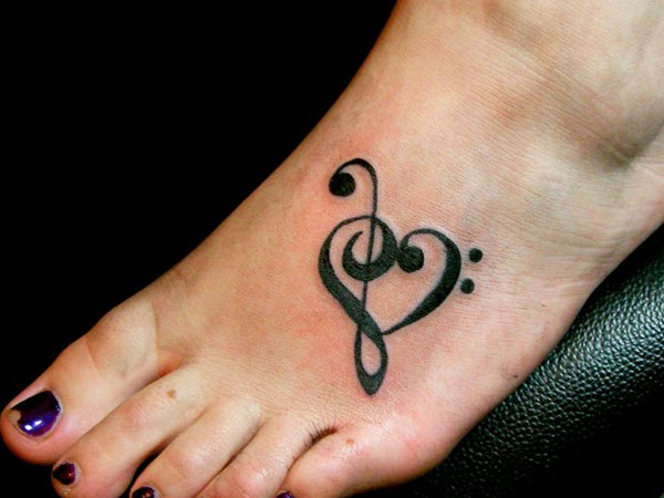 this foot tattoo for women combines love and music in a heart shaped ...