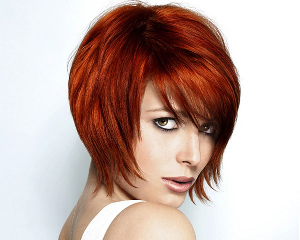 thick hair colored with red shade and styled in choppy sharp layers