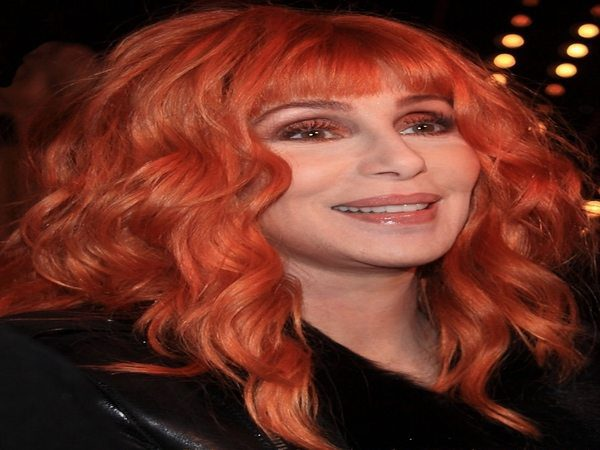 Cher with Shoulder Length Curly Light Red Hair