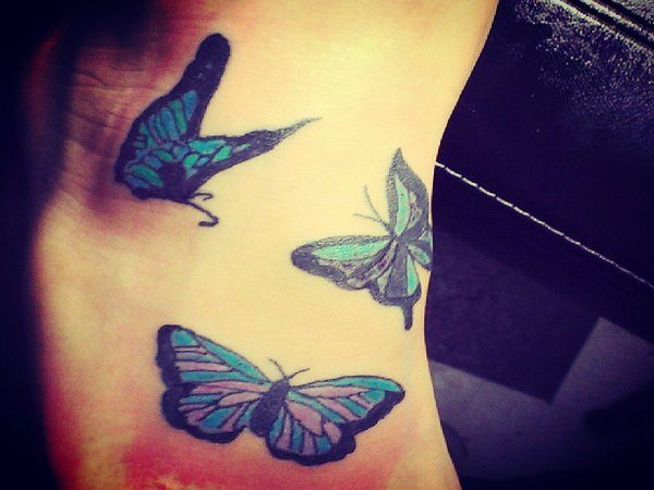 Three Blue Butterflies Flying Around Top of Foot