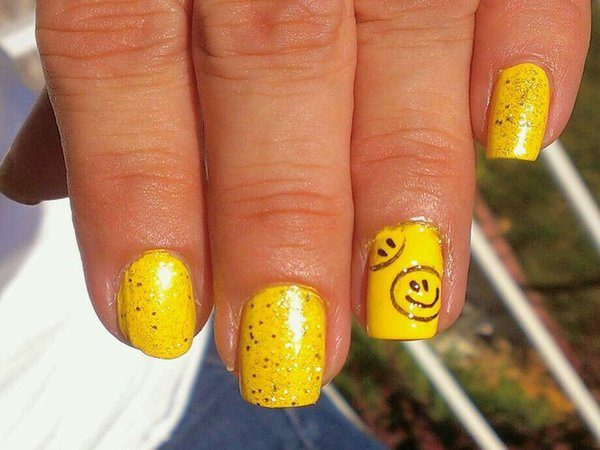Yellow Glitter Nails with One Nail Smiley Faces