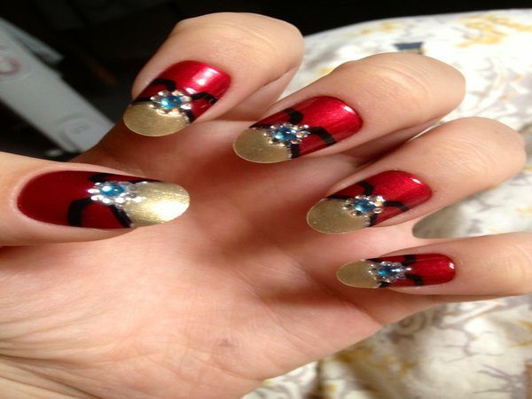 Red Nails with Gold Tips, Black Lines, and Blue Rhinestones