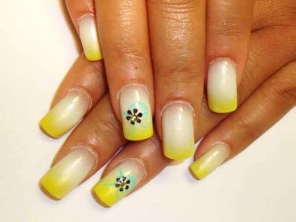 White Nails with Yellow Tips and Black Flowers on One Nail