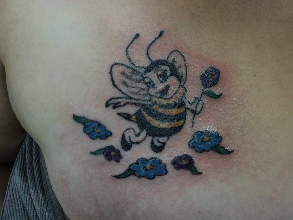 Lady Bee Holding Purple Flower and Surrounded By Purple and Blue Flowers Tattoo