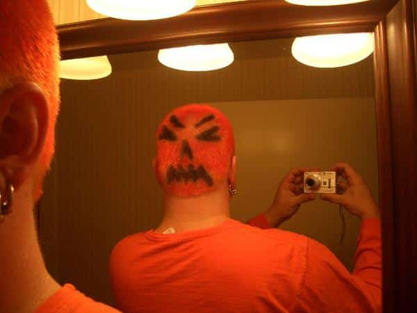 Shaved Head Painted Orange with Black Eyes, Nose and Mouth Design