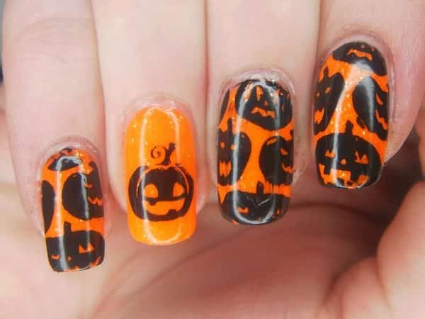 Orange Glitter Nails with Multiple Black Pumpkin Decorations