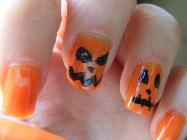 Orange Nails with Two Nails Decorated with Black Faces