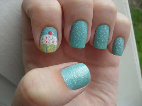Light Blue Nails with White Glitter and White Cupcake Design