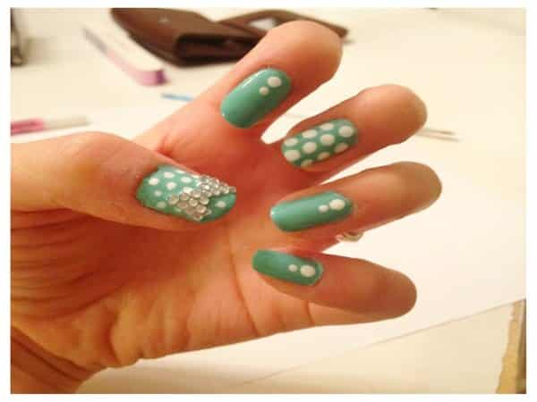 Pale Green Nails with White Spots and a Rhinestone Bow Tie