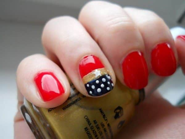 Red Nails with One Nail with a Gold Stripe and Blue Tip Decorated with White Dots