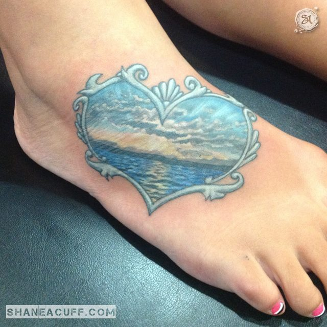 0daf27bde9ae5 A Bright Blue Ocean Sunset Foot Tattoo, Wrapped Inside A Heart Shaped Frame