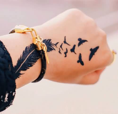 Flying birds and feather hand tattoos for women